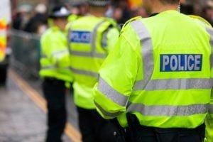 Des policiers en gilet de haute visibilité contrôlent la foule lors d'un événement au Royaume-Uni.